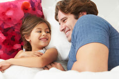 Pai And Daughter Lying na cama junto Foto de Stock Royalty Free