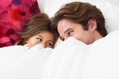 Pai And Daughter Lying na cama junto Foto de Stock