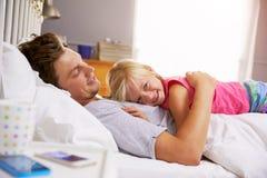 Pai And Daughter Lying na cama junto Imagens de Stock