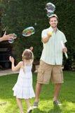 Pai And Daughter Playing com bolhas no jardim Fotografia de Stock
