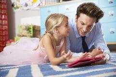 Pai And Daughter Playing no quarto com tabuleta de Digitas Fotos de Stock Royalty Free