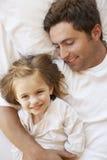 Pai And Daughter Relaxing na cama Imagem de Stock
