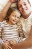Pai And Daughter Relaxing na cama Fotos de Stock