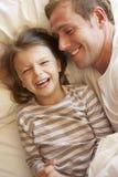 Pai And Daughter Relaxing na cama Imagens de Stock
