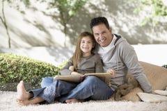 Pai And Daughter Sitting com álbum de fotografias Fotos de Stock Royalty Free