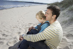 Pai And Daughter Sitting em Sandy Beach Imagens de Stock
