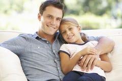 Pai And Daughter Sitting em Sofa At Home Foto de Stock