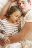 Pai And Daughter Sleeping na cama Imagem de Stock