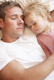 Pai And Daughter Sleeping na cama Fotografia de Stock Royalty Free