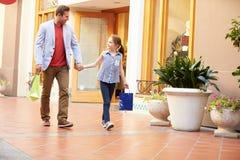 Pai And Daughter Walking através da alameda com sacos de compras Imagens de Stock