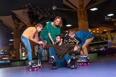 pai de ajuda da família nos patins de rolo a levantar-se fotografia de stock