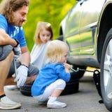 Pai de ajuda da menina para mudar uma roda de carro Imagens de Stock