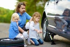 Pai de ajuda da menina para mudar uma roda de carro Imagem de Stock