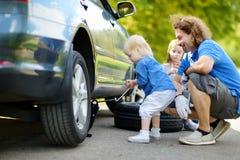 Pai de ajuda da menina para mudar uma roda de carro Imagem de Stock Royalty Free