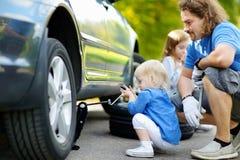 Pai de ajuda da menina para mudar uma roda de carro Imagens de Stock Royalty Free