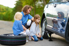 Pai de ajuda da menina para mudar uma roda de carro Foto de Stock