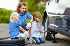 Pai de ajuda da menina para mudar uma roda de carro Foto de Stock Royalty Free