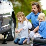 Pai de ajuda da menina para mudar uma roda de carro Fotografia de Stock