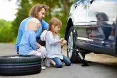 Pai de ajuda da menina para mudar uma roda de carro Fotos de Stock Royalty Free