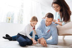 Pai de inquietação agradável que faz com sua filha um enigma de serra de vaivém fotografia de stock royalty free