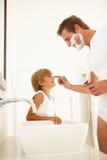 Pai de observação do filho que raspa no espelho do banheiro Fotos de Stock Royalty Free