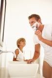 Pai de observação do filho que raspa no espelho do banheiro Fotografia de Stock
