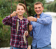 Pai de riso com o filho que olha peixes no gancho Fotografia de Stock Royalty Free