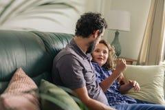 Pai de sorriso e filho novo que falam junto em seu sofá fotografia de stock