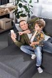 pai de sorriso e filho pequeno que usa o smartphone ao descansar no sofá fotografia de stock