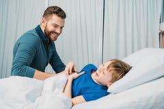 Pai de sorriso que joga com o rapaz pequeno doente que encontra-se na cama de hospital foto de stock