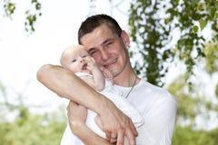 Pai de sorriso que prende seu bebé Fotos de Stock