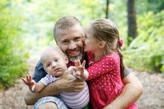 Pai devotado que abraça seus filho e filha, apreciando o exterior imagens de stock