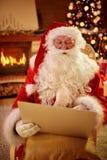 Pai do Natal em sua sala de visitas com portátil Imagem de Stock
