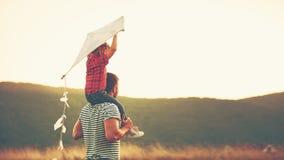 Pai e criança felizes da família no prado com um papagaio no verão