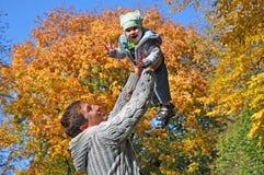 Pai e criança felizes no fundo outonal imagem de stock