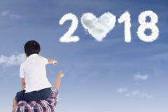 Pai e criança que apontam nos números 2018 Fotos de Stock