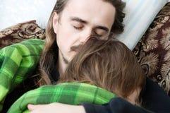 Pai e criança que dormem em casa junto na poltrona Descanso da família Paternidade feliz, paternidade Paizinho e filha Imagens de Stock Royalty Free