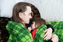 Pai e criança que dormem junto na poltrona Descanso da família Paternidade feliz, paternidade Paizinho e filha envolvidos na cobe Imagem de Stock Royalty Free