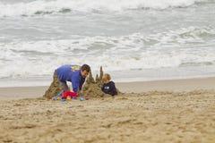 Pai e criança que jogam na praia Foto de Stock