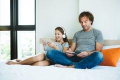 Pai e criança que jogam na tabuleta fotografia de stock