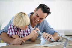 Pai e criança que montam um brinquedo plano imagem de stock