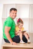 Pai e criança que usa a tabuleta eletrônica em casa Fotos de Stock Royalty Free
