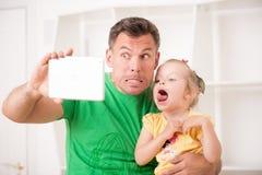 Pai e criança que usa a tabuleta eletrônica em casa Fotografia de Stock