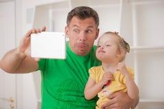 Pai e criança que usa a tabuleta eletrônica em casa Imagem de Stock