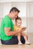 Pai e criança que usa a tabuleta eletrônica em casa Fotografia de Stock Royalty Free