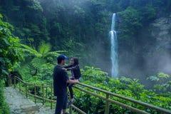 Pai e criança que vagam na cachoeira de Pelangi fotografia de stock royalty free