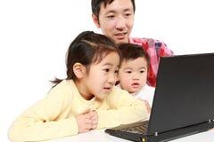 Pai e crianças no laptop Imagem de Stock Royalty Free