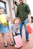 Pai e crianças que enganam ao redor com sacos de compras coloridos Foto de Stock Royalty Free