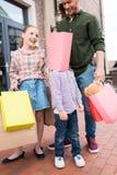 Pai e crianças que estão e que enganam ao redor com sacos de compras coloridos Fotos de Stock Royalty Free