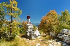 Pai e crianças que exploram a floresta de pedra, formação de rocha natural, criada pelas camadas múltiplas de pedra, situadas per imagem de stock